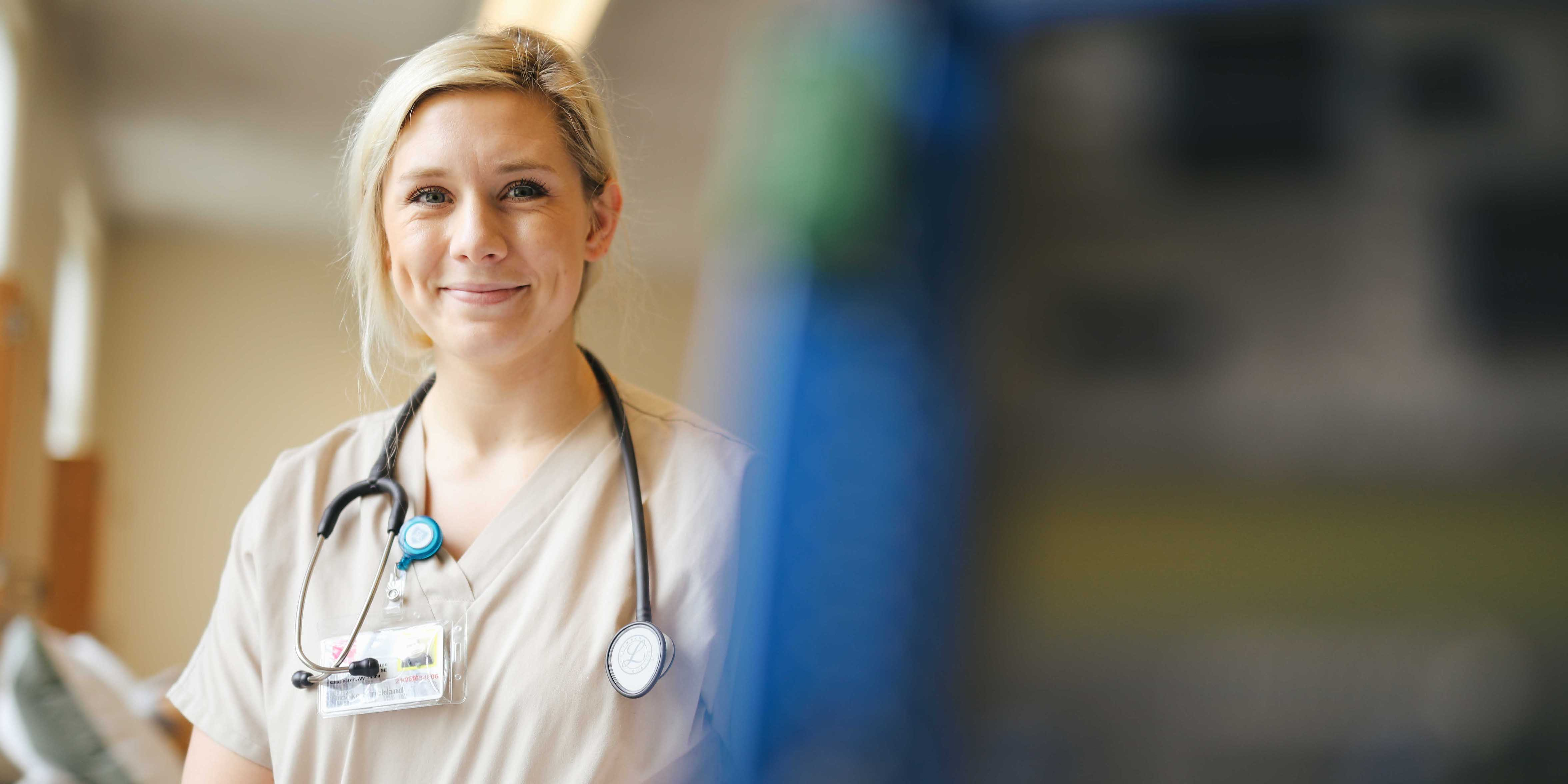 female nursing student smiling in scrubs with stethoscope