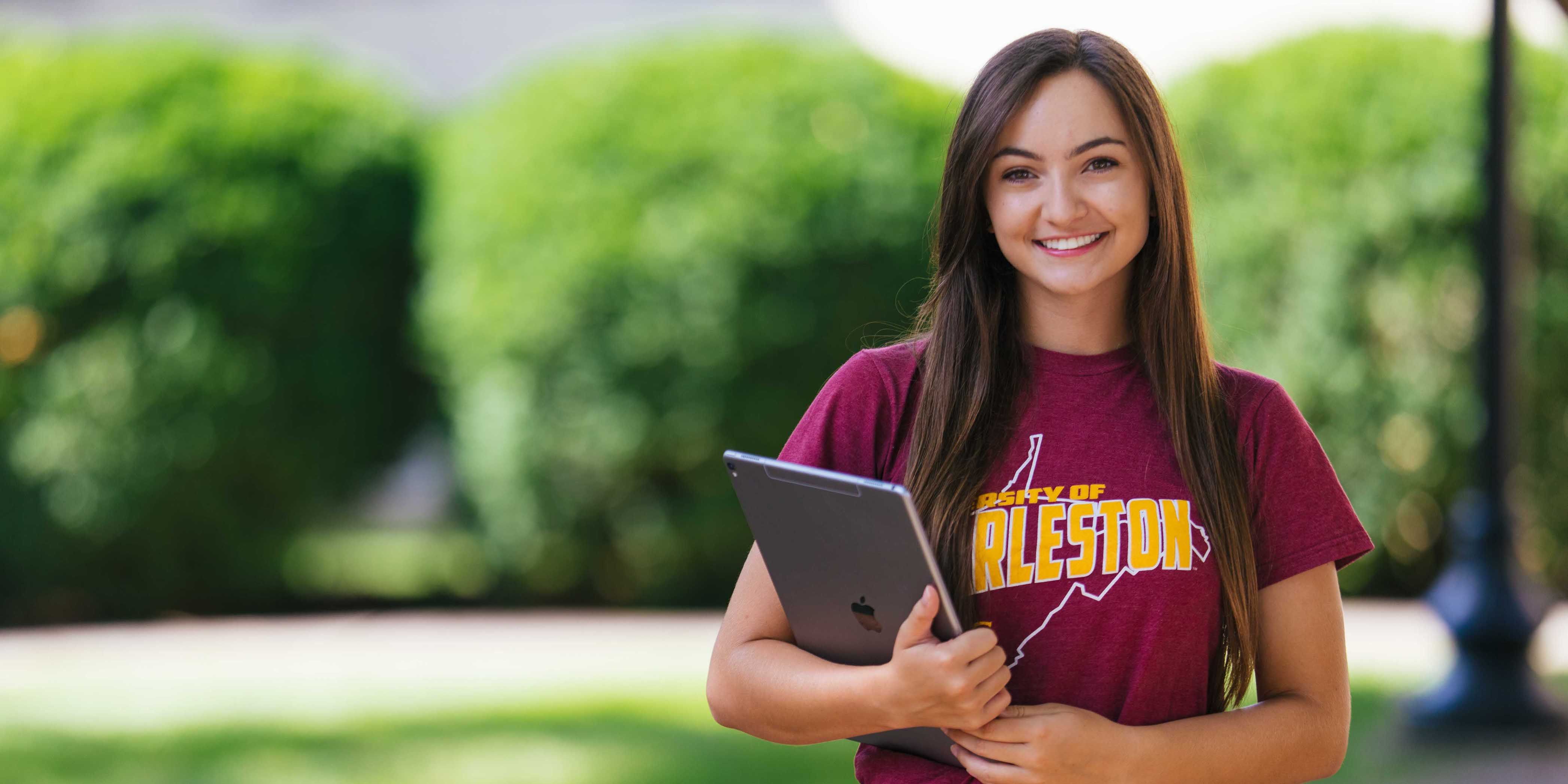 smiling female student posing with tablet