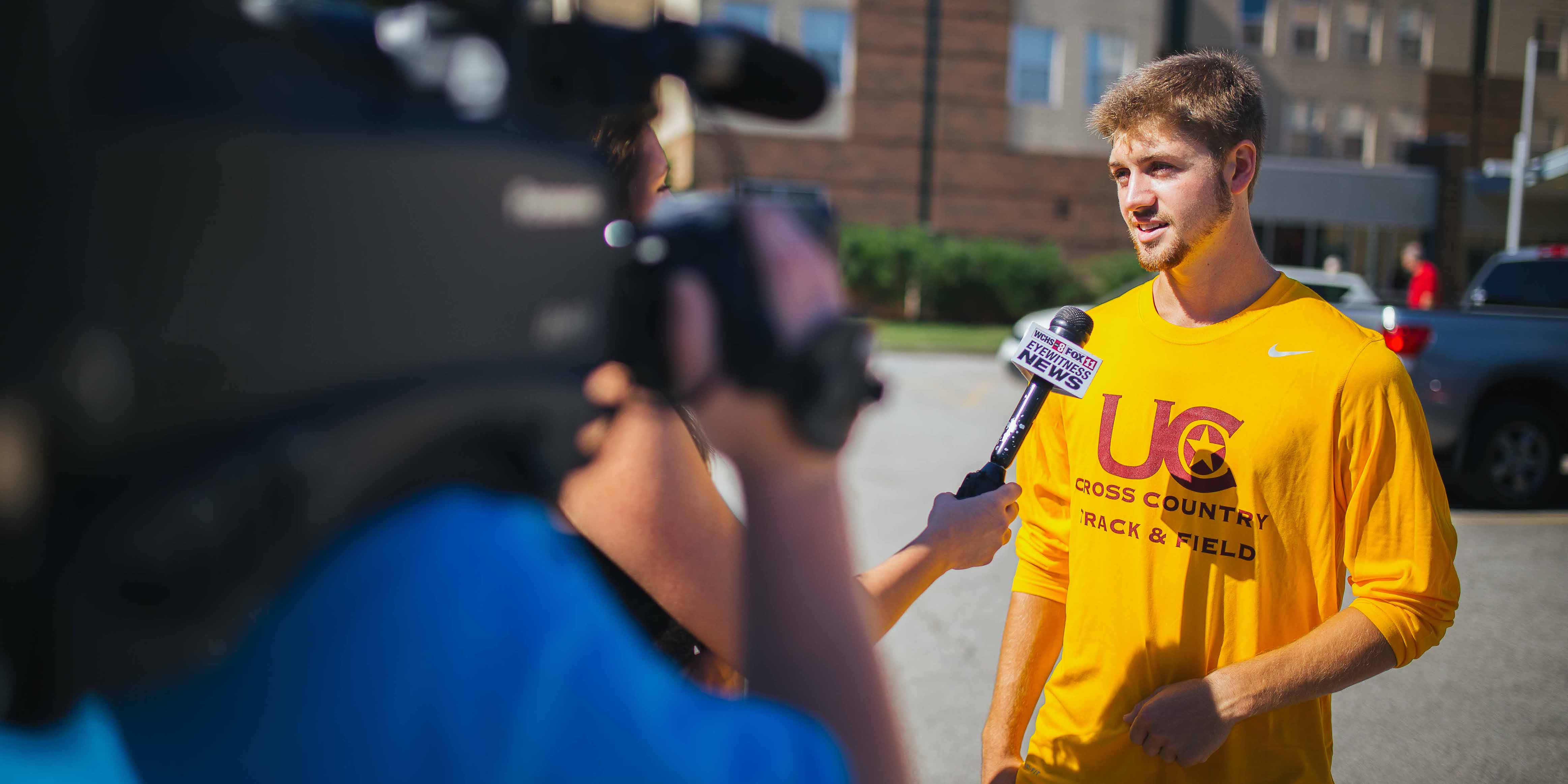 male student athlete being interviewed by local news anchor