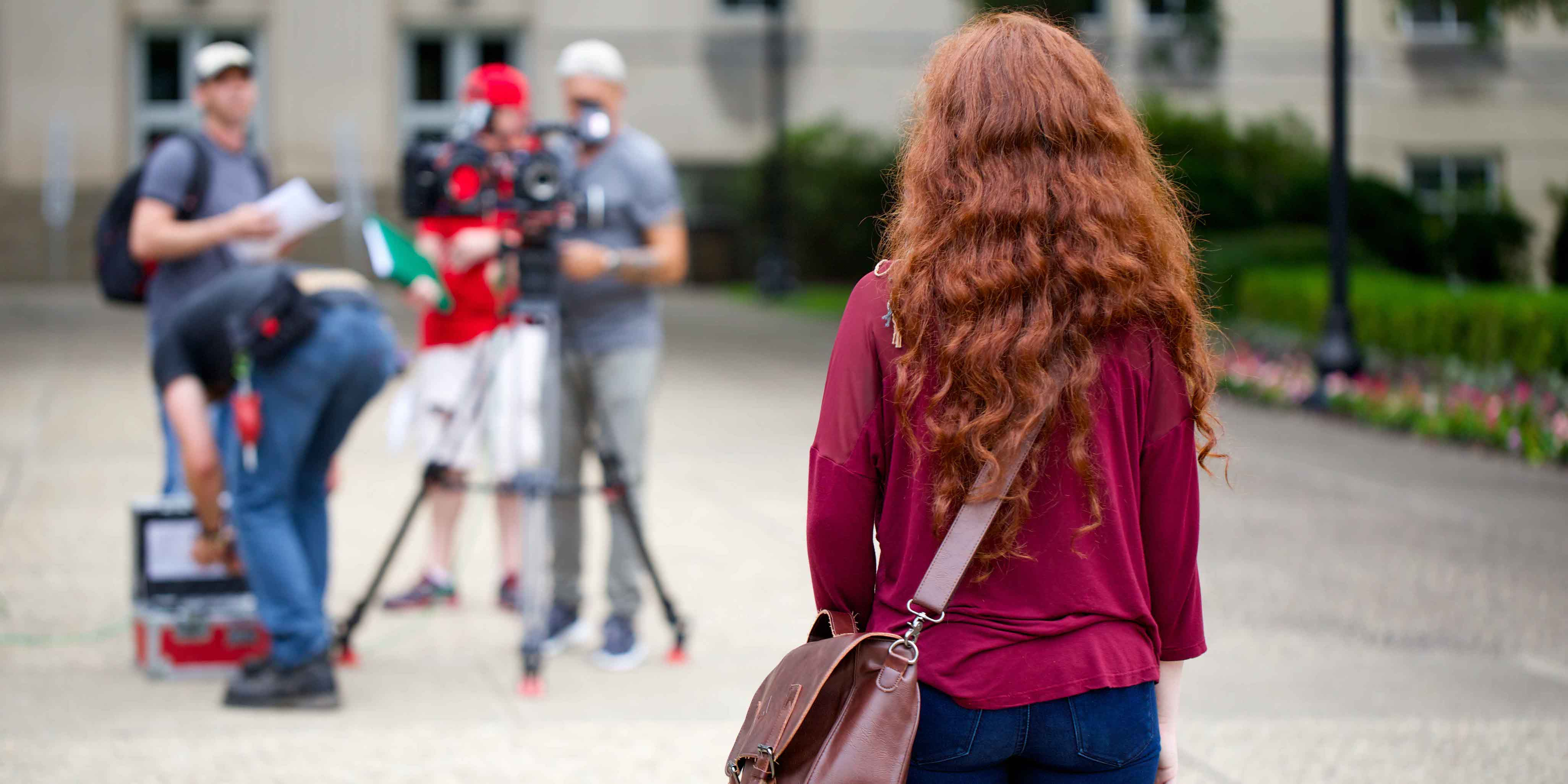 female student with messenger bag facing away from camera