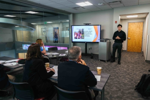 male student presenting a powerpoint slide to business professionals in a classroom