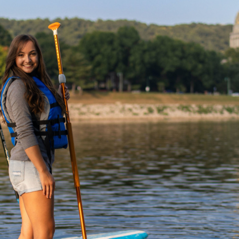 male and female student posing on paddle boards in river with Capitol in background