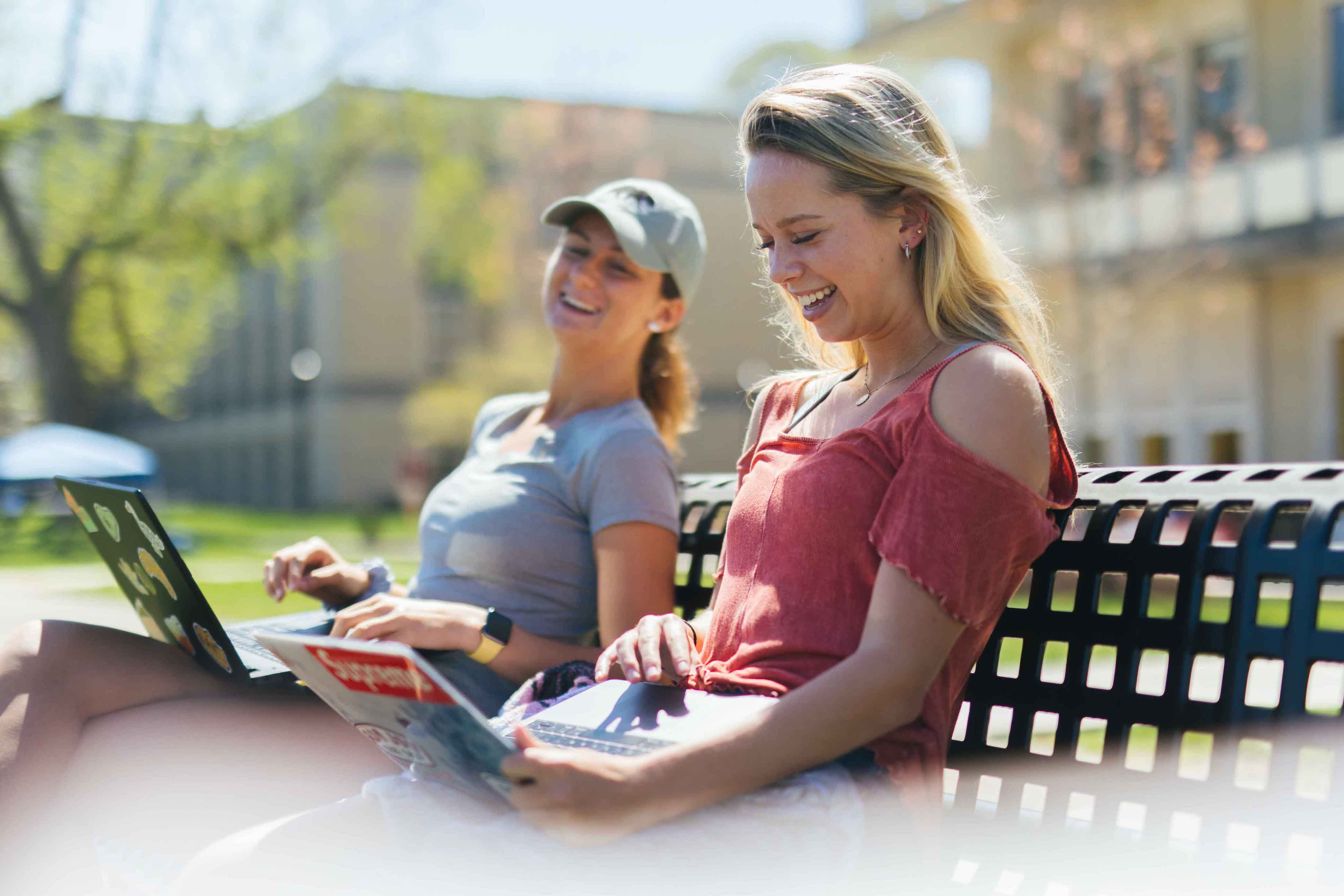two females laughing outside on a bench while using laptops