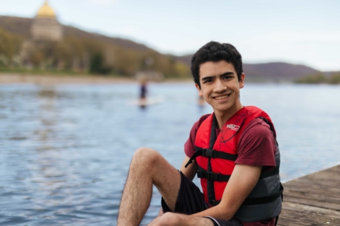 Male student sitting on boat dock at the river wearing a life jacket
