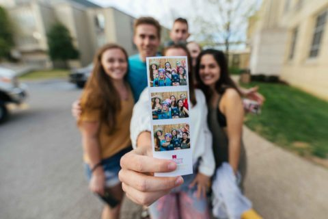 male and female students standing together while female student holds up three photobooth pictures of the group