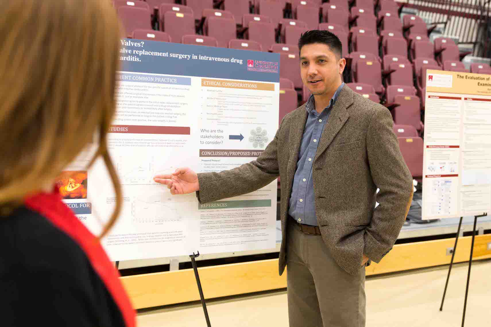 Male student in professional attire pointing to and discussing his research poster