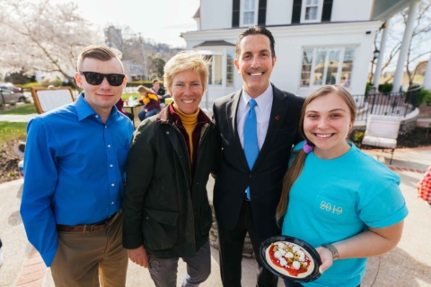 Two students posing with President Roth and Lynn during SGA and SBA event at President's house