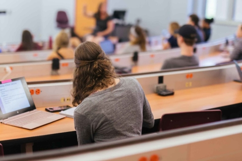 back view of female student taking notes during class lecture