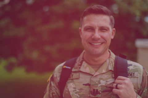 Smiling male in Army fatigues wearing a backpack