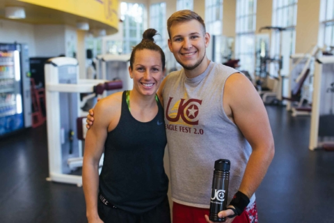 male and female in workout apparel posing in fitness center