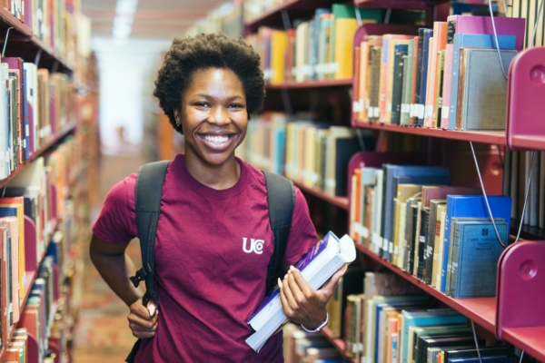 smiling student with backpack and books in the library stacks