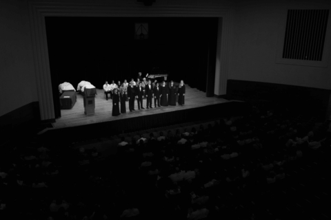 balcony view of UC choral group performing on stage at pharmacy event