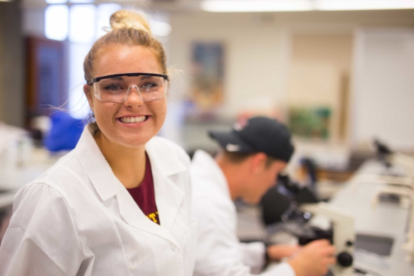 smiling female student in lab wearing lab coat and safety glasses