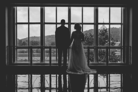 back view of bride and groom standing in front of window overlooking capitol dome