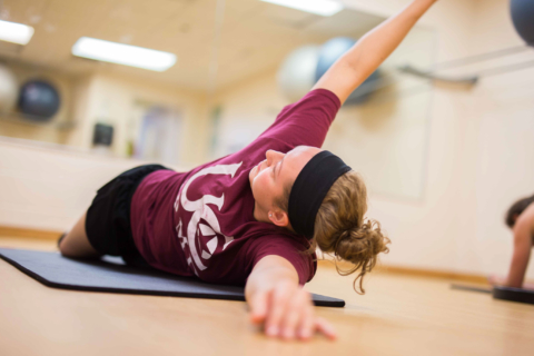 female student doing yoga pose on floor
