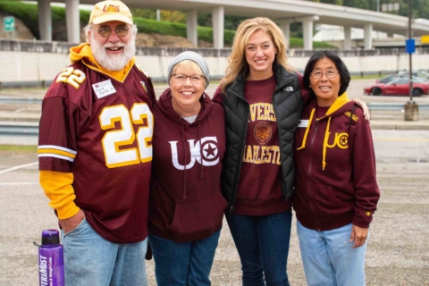 Alumni posing for a photo while wearing UC apparel.