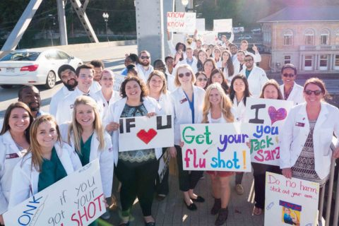 Group of pharmacy students in lab coats standing on bridge with signs to promote getting your flu shot