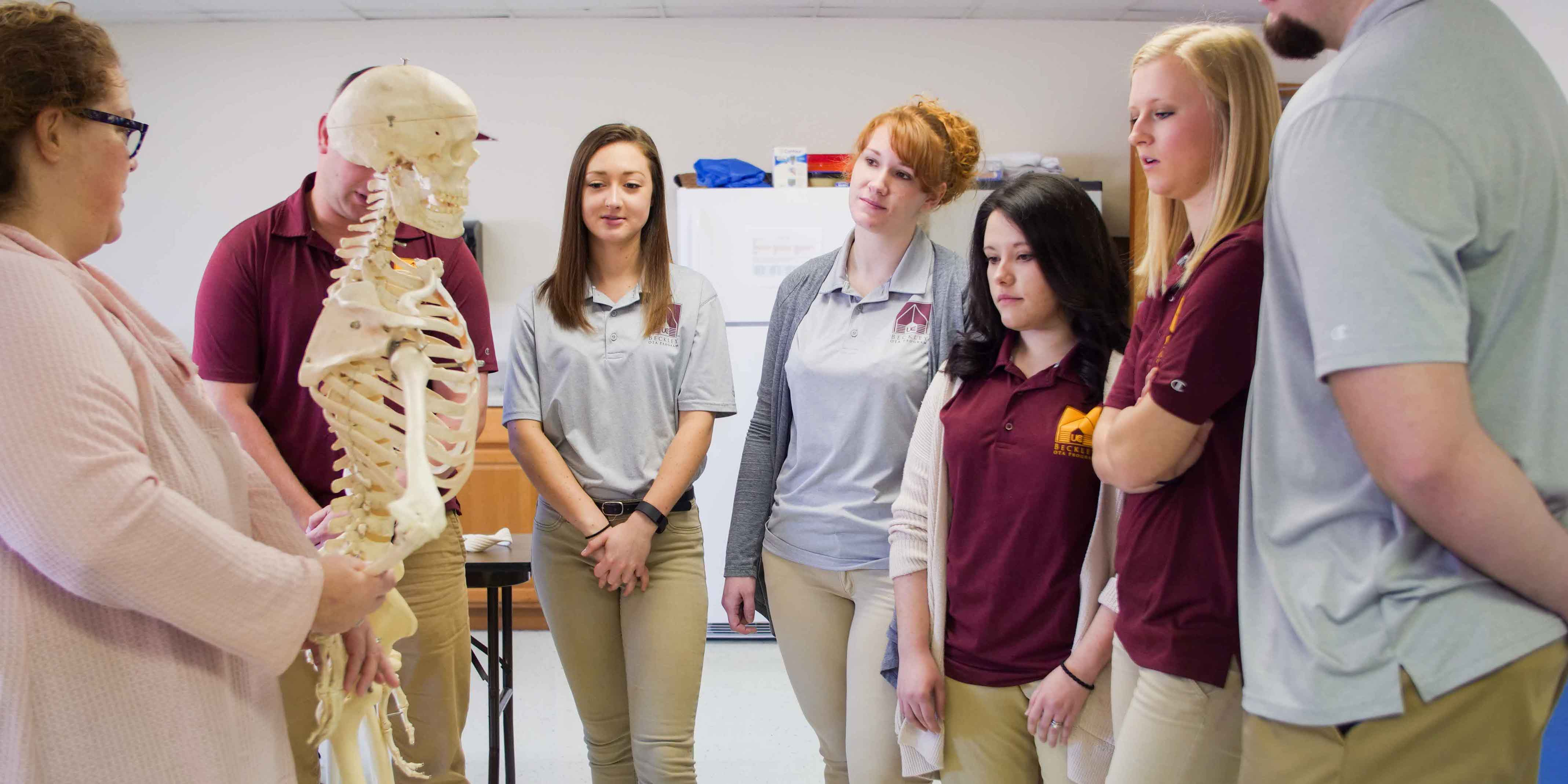 Group of Occupational Therapy Assistant students looking at skeleton while professor instructs