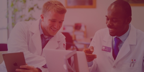 two male pharmacy students in lab coats working on tablet and computer