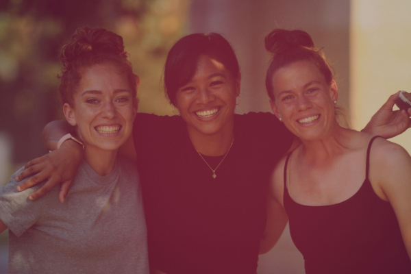 Three smiling females with arms locked and posing for photo