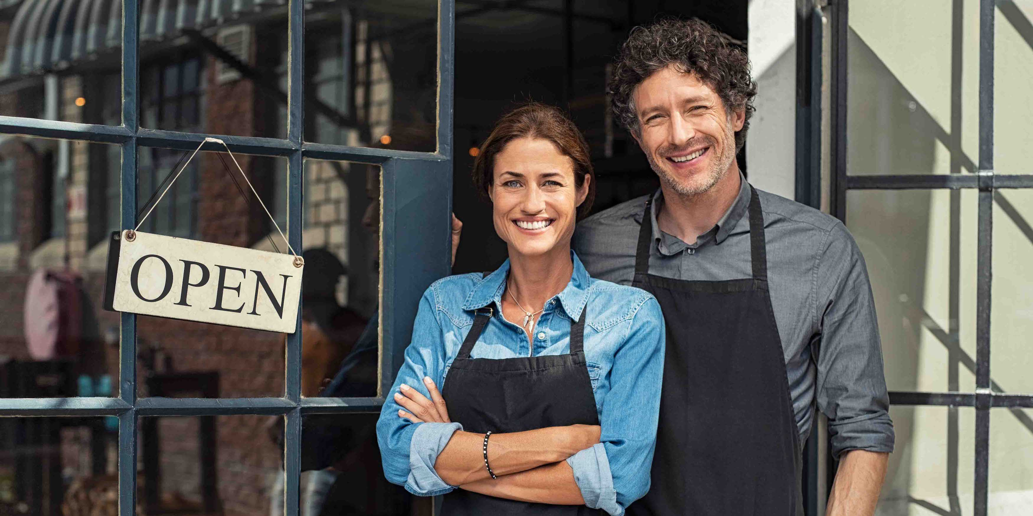 Two cheerful small business owners smiling and looking at camera while standing at entrance door.