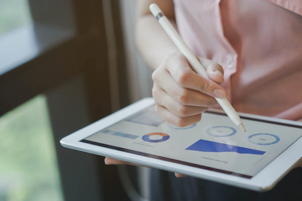 close up on businesswoman hand using stylus pen for writing on screen dashboard tablet