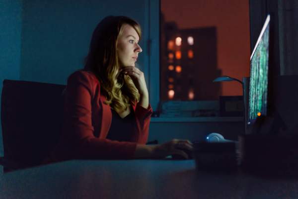 Side view of businesswoman working on a computer at night.