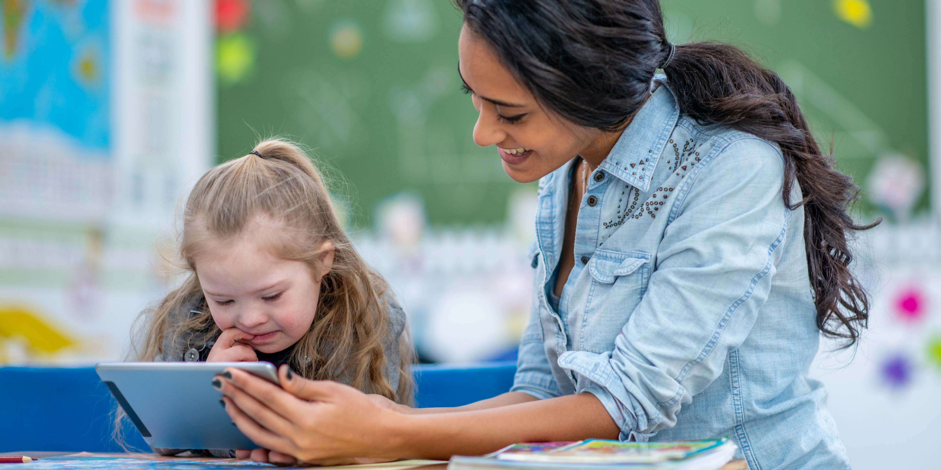 female holding an ipad while child looks at it