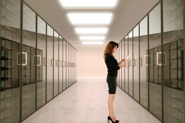 female dressed in business attire looking at tablet while standing in front of server bank