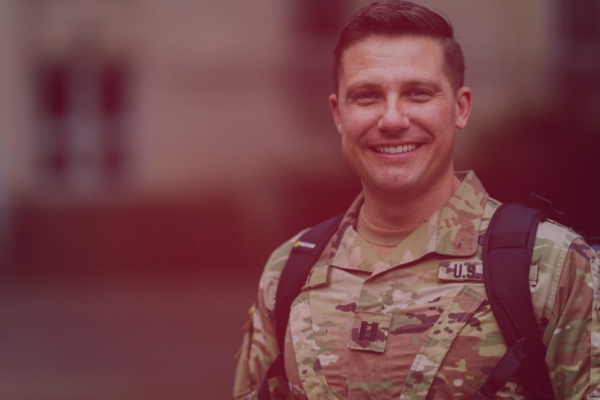 smiling male in Army fatigues with a backpack