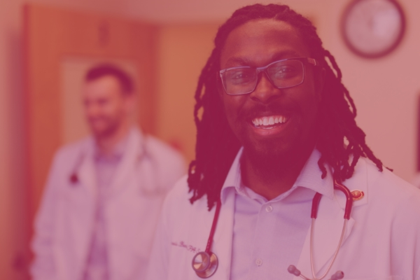 smiling male physician assistant student in lab coat with stethoscope over shoulders
