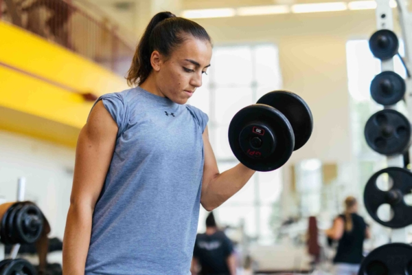 Female in gym lifting weights