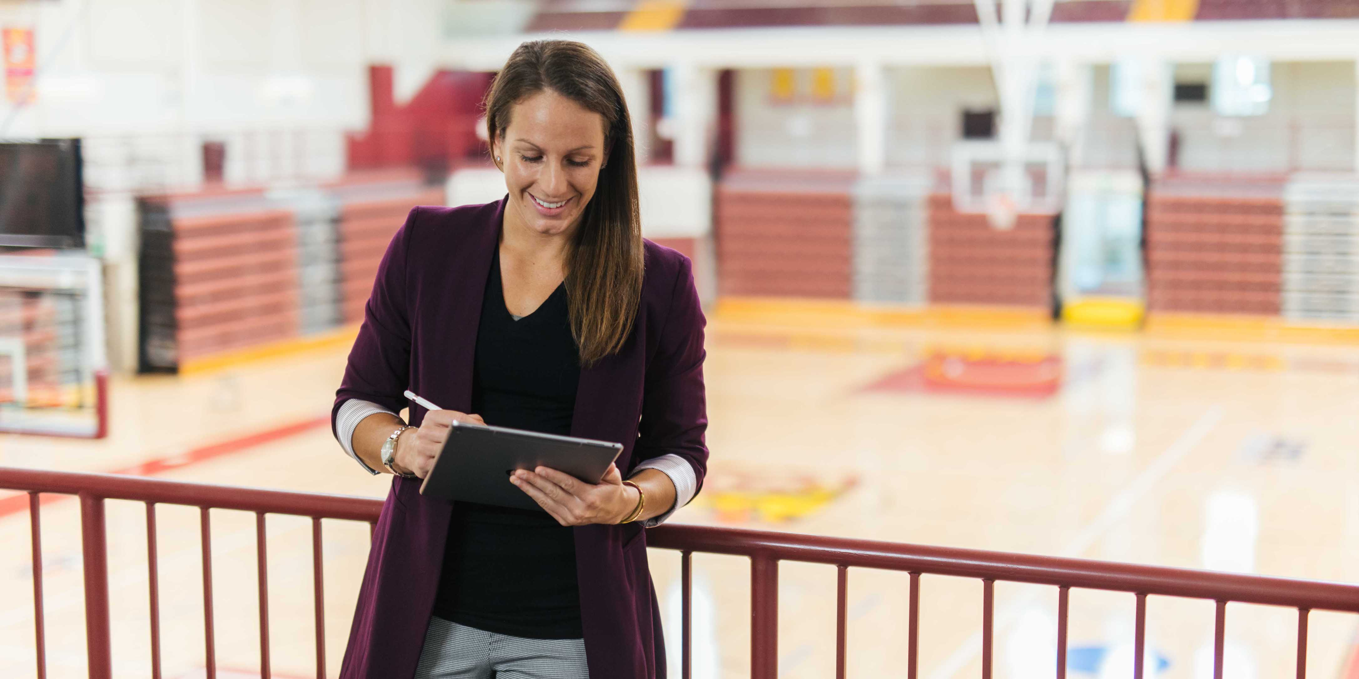 female with tablet in basketball arena