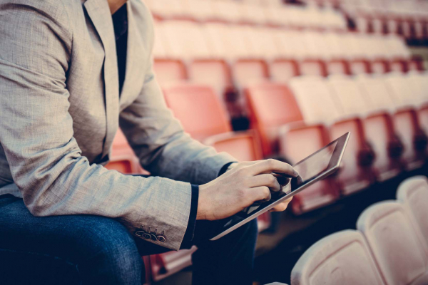 Young and successful football manager working on a tablet, and sitting on the stands alone. Cropped photo.