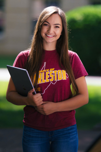college student holding a tablet smiling Charleston